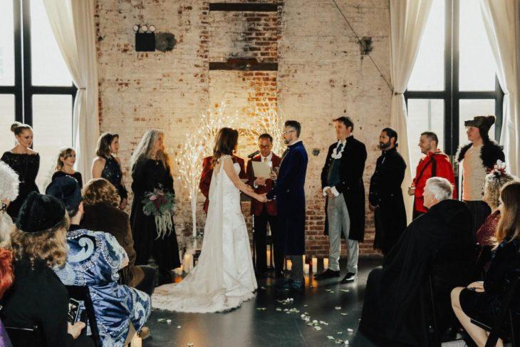 Novios se casan en boda inspirada en Harry Potter; esposa con vestido blanco y esposo con traje azul con invitados