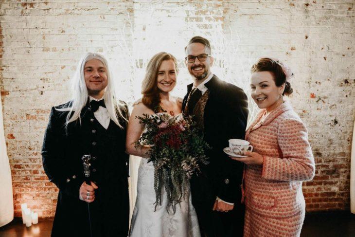 Novios se casan en boda inspirada en Harry Potter; novia con vestido blanco, novio con traje azul, invitados disfrazados de Lucius Malfoy y Dolores Umbridge