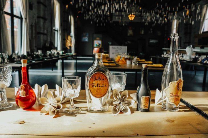 Novios se casan en boda inspirada en Harry Potter; mesa con copas, flores de papel y pócima Felix Felicis