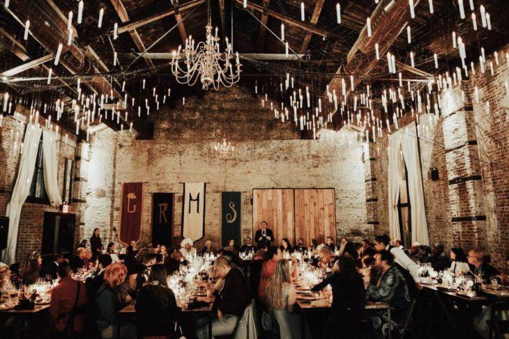 Novios se casan en boda inspirada en Harry Potter; comedor adornado como Hogwarts, con velas colgando del techo y un gran candelabro; invitados comiendo en las mesas
