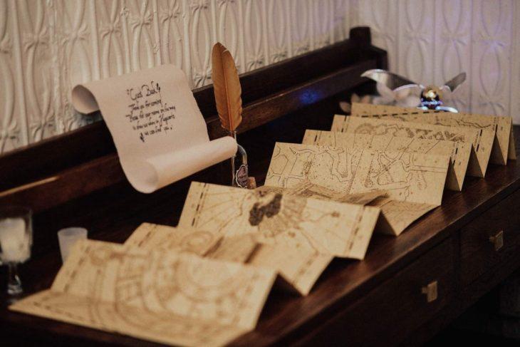 Novios se casan en boda inspirada en Harry Potter; libro de firmas que parece el mapa del merodeador con una pluma para escribir