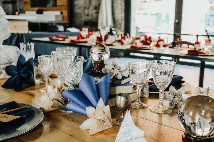 Novios se casan en boda inspirada en Harry Potter; mesa adornada con copas, libros, bola de nieve y flores de papel