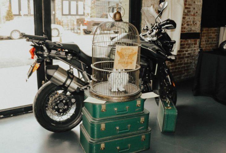 Novios se casan en boda inspirada en Harry Potter; jaula con lechuza blanca Hedwig, sobre maletas verdes y la motocicleta de Sirius Black