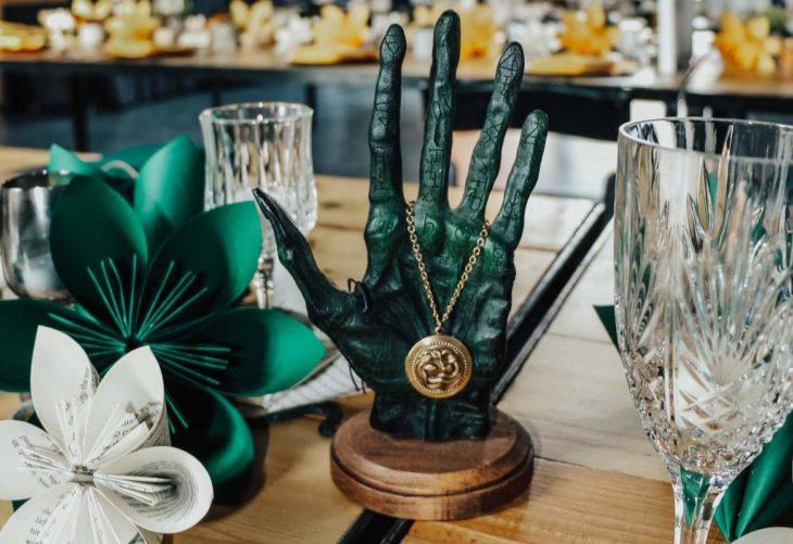 Novios se casan en boda inspirada en Harry Potter; adornos de mesa, flores de papel, copas de vidrio y la mano de la gloria
