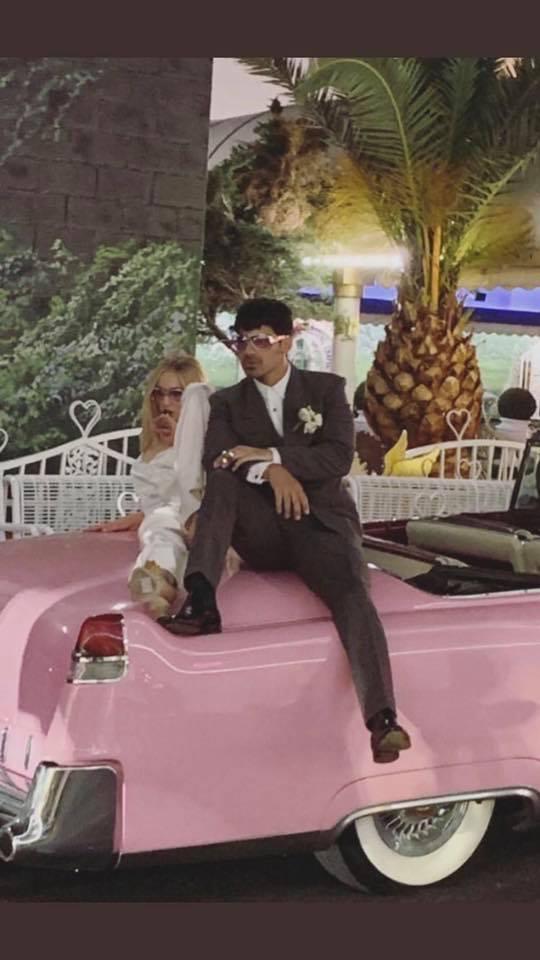Joe Jonas y Sophie Turner después de su boda en las Vegas sentados en un automóvil de color rosa posando para una foto