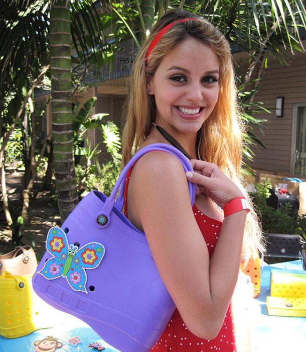 Chica sosteniendo en sus hombros una bolsa morada con forma de sandalia Croc en color morado