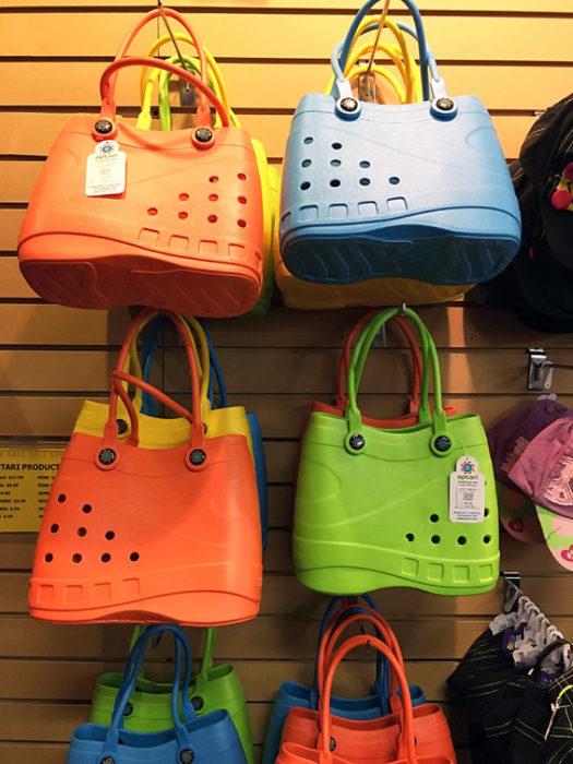 Bolsas inspiradas en las sandalias Crocs de diferentes colores colgadas en un estante