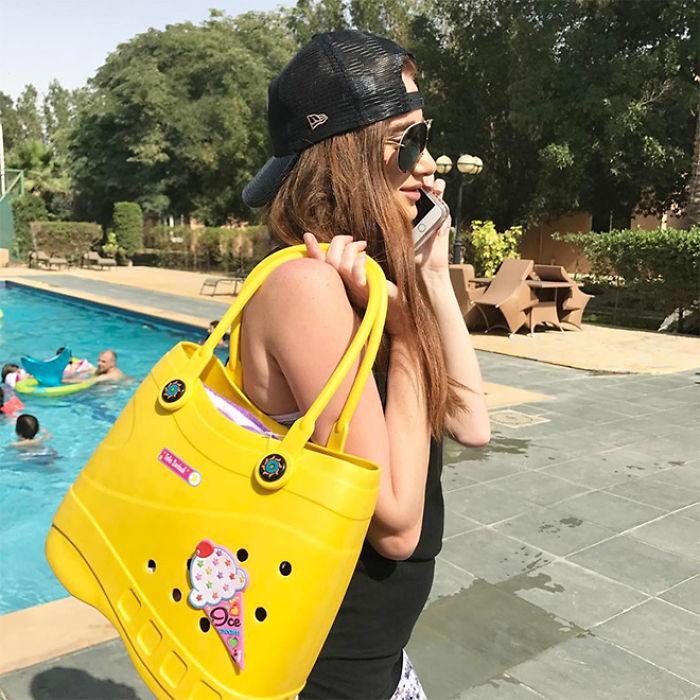 Chica hablando por celular mientras presume su bolsa Crocs en tono amarillo y con un helado que la adorna