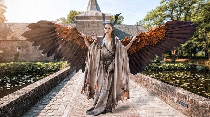 Chica vestida de Maléfica con sus enormes alas caminando por un enorme castillo