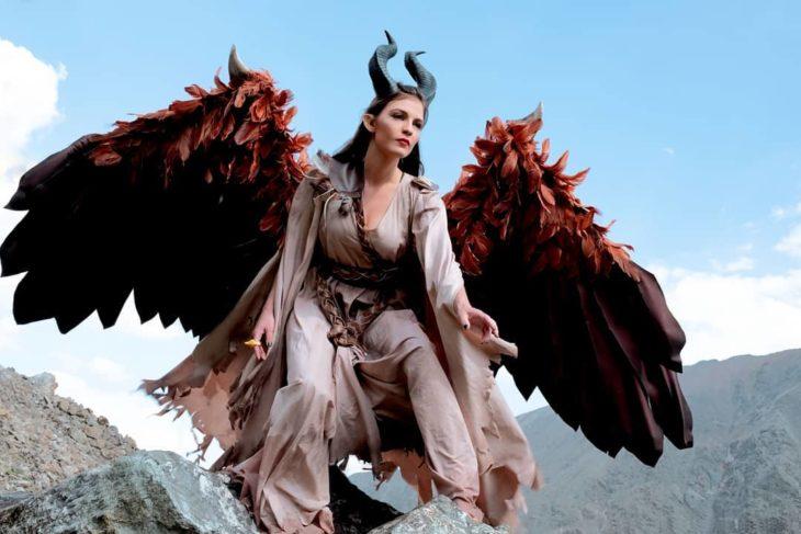 Chica vestida de Maléfica para asistir a la convención de Comic Con. Esta parada sobre una roca, usando unas enormes alas y un traje de color café