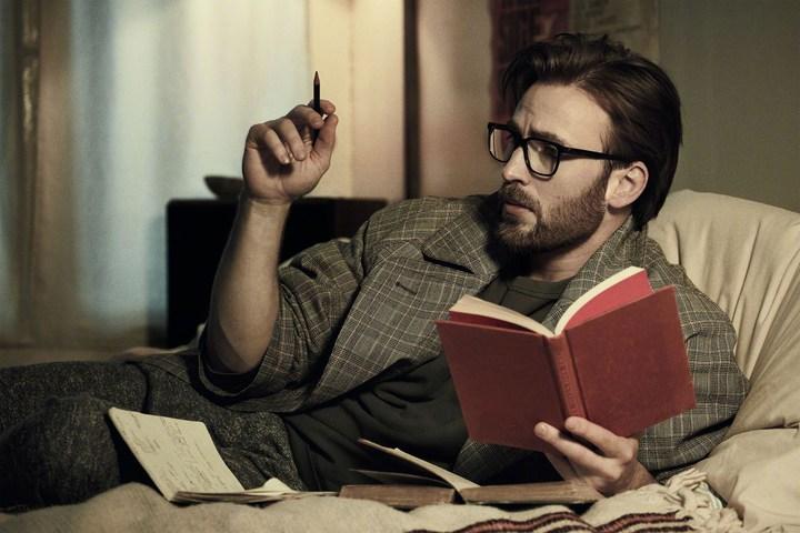 Chris Evans con lentes y un libro rojo en las manos