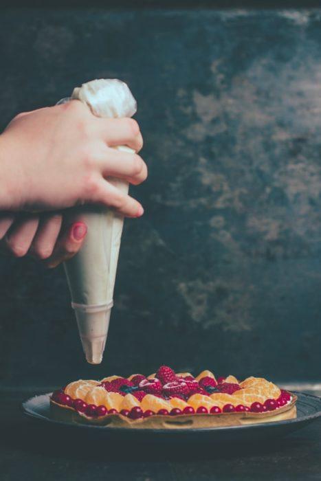 manos de mujer decorando una tarta