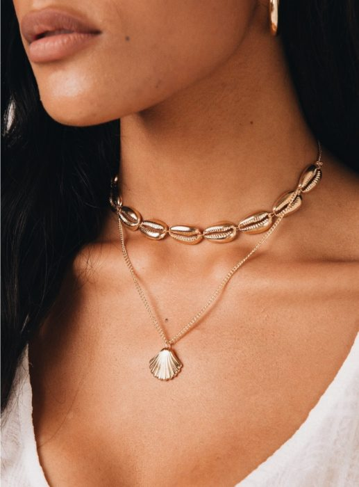 Chica usando un collar de conchas en color dorado