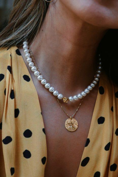 Chica usando un collar de perlas de marca versace