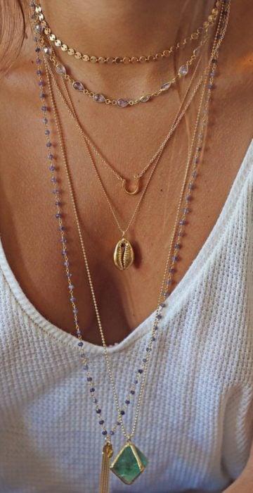 Chica usando un collar que tiene conchas de mar