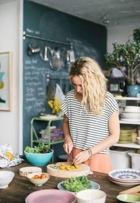 Mujer rubia en cocina preparando alimentos sanos