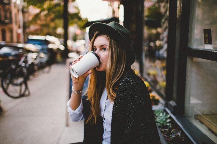 mujer bebiendo café caliente fuera de la cafetería