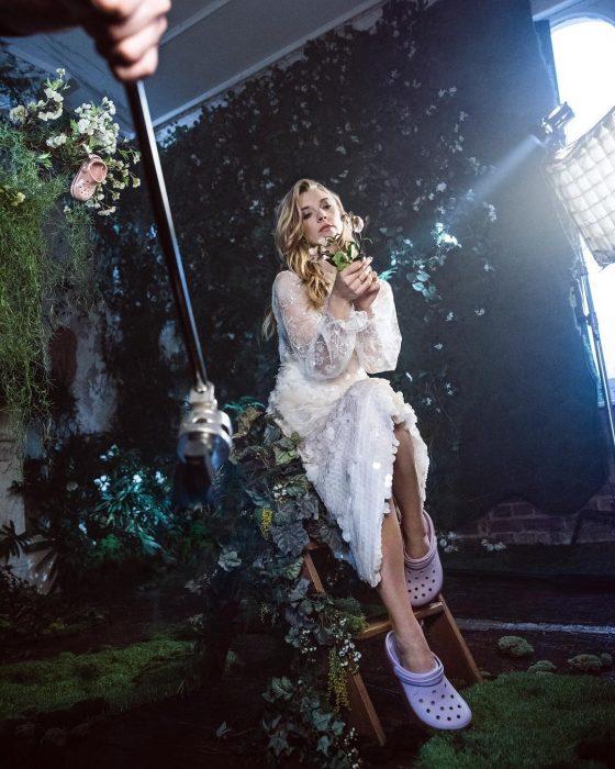 Actriz Natalie Dormer, mujer rubia con vestido blanco de lentejuelas y encaje, usando crocs blancos para boda, en sesión de fotos con plantas y vegetación