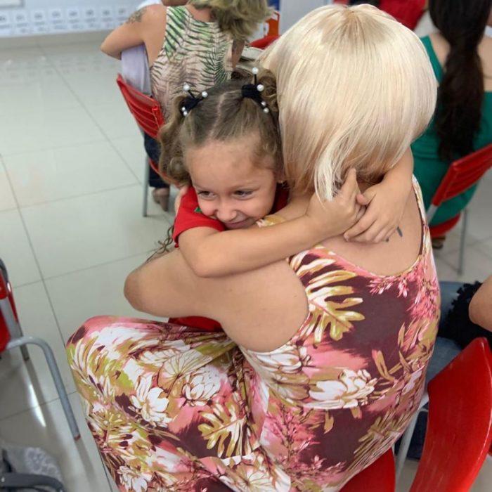 Daniel Correa, papá viudo de una niña, se disfraza de mujer para asistir al festival del Día de las Madres de la escuela, con barba rosa, peluca rubia y vestido floreado; papá abrazando a su hija