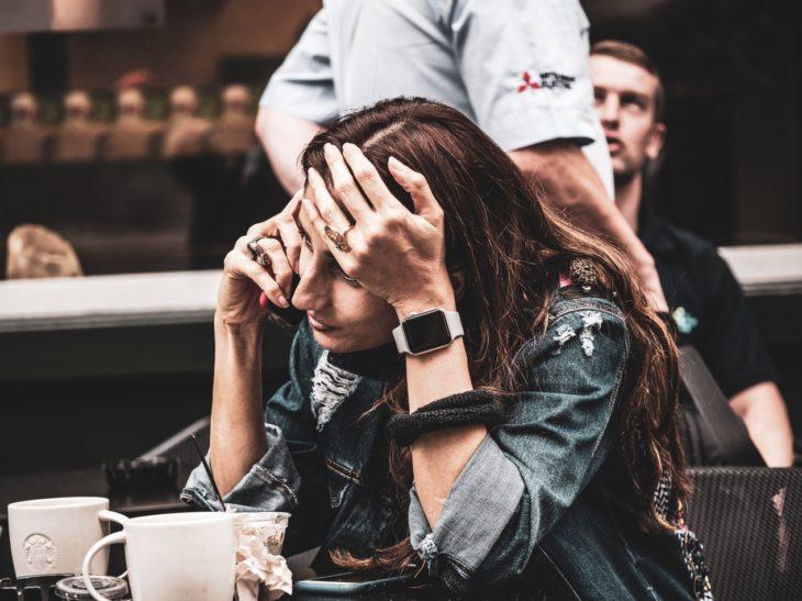 Chica hablando por celular con la mano en la frente con gesto de preocupación