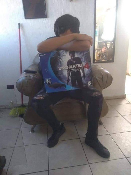 Chico abrazando a un Play Station 4 mientras llora porque se tiene que despedir de él