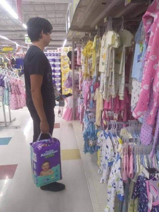 Chico parado frente a la ropa de bebé en un supermercado