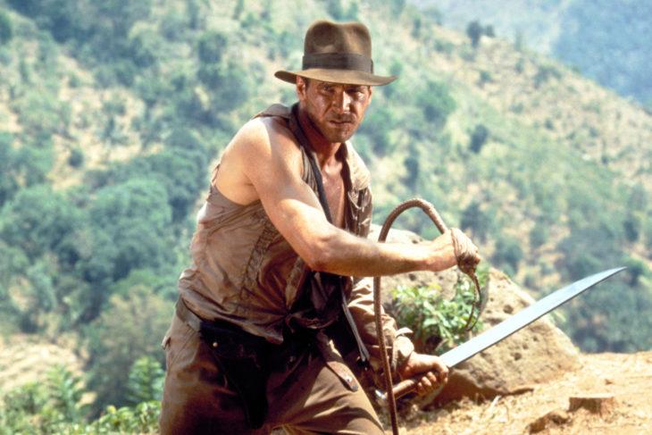 Escena de la película Indiana Jones con Harrison Ford sosteniendo un latigo y una espada listo para pelear