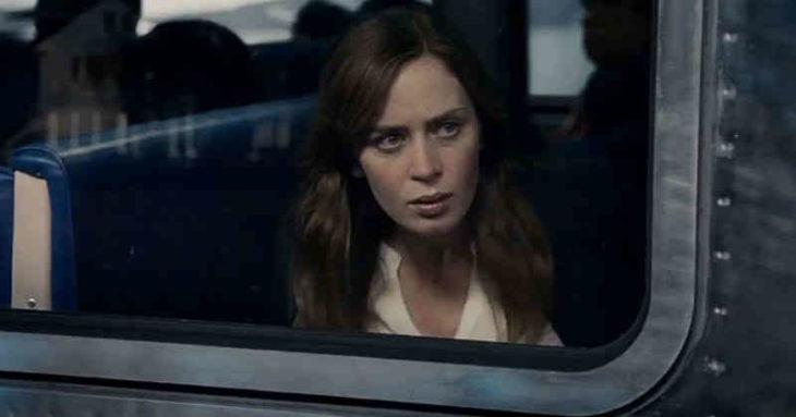 Mujer mirando a través de la ventanilla de un tren en movimiento, escena de la película La chica del tren
