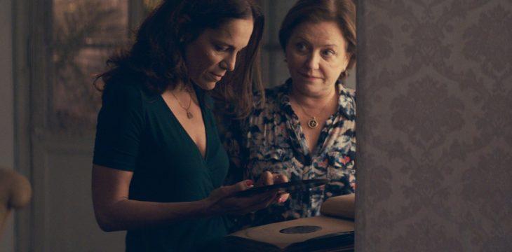 Dos mujeres leyendo un diario, sorprendidas y consternadas, escena de la película Las Herederas