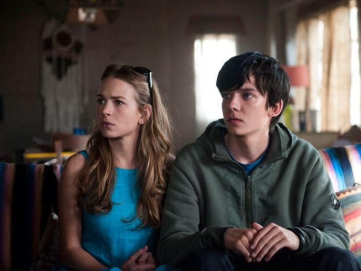 Asa Butterfield y Britt Robertson sentados en un sofá, escena de la película El espacio entre nosotros