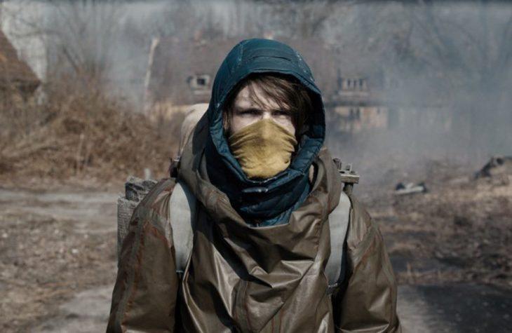 Louis Hoffman son el rostro cubierto caminando por un bosque seco, escena de la serie Dark