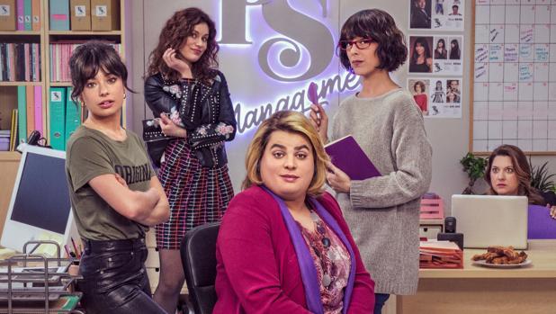 Grupo de mujeres en una oficina gris con detalles morados, posando para una fotografía, escena de la serie Paquita Salas,tercera temporada