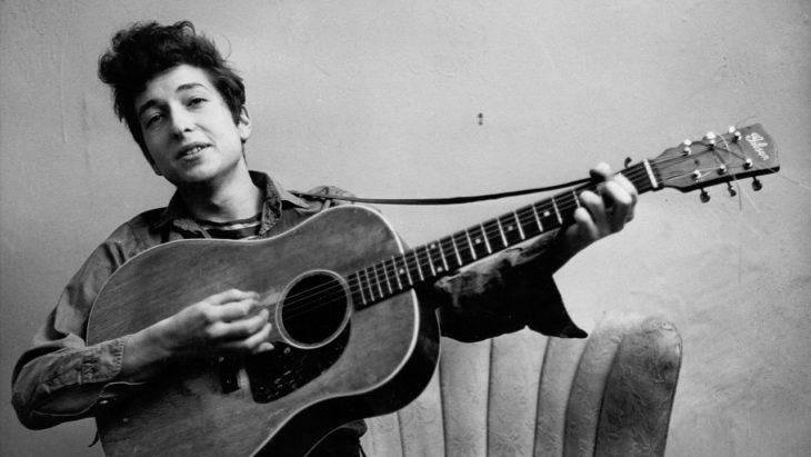 Bob Dylan tocando la guitarra sentado en un sofá, Rolling Thunder Revue: A Bob Dylan Story By Martin Scorsese