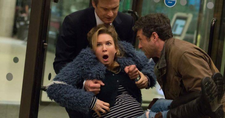 Dos hombres cargando a una mujer embarazada, escena de la película El bebé de Bridget Jones
