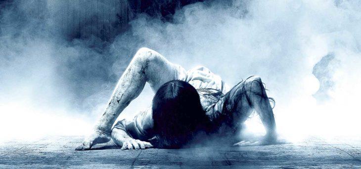 Mujer de cabello largo y vestido blanco arrastrándose por el piso, escena de la película El Aro 3