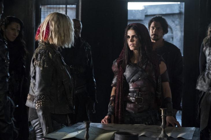 Grupo de personas reunidas en una sala, discutiendo, escena de la serie Los 100, quinta temporada