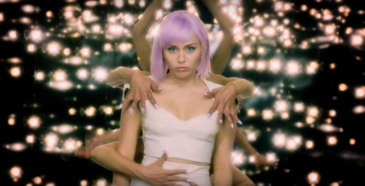 Chica usando una peluca lila, siendo abrazada por diversas personas, escena de la serie Black Mirror, quinta temporada