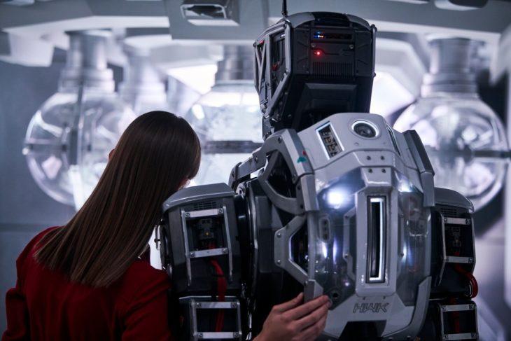 Chica recargada sobre el hombro de un robot, escena de la película I Am Mother