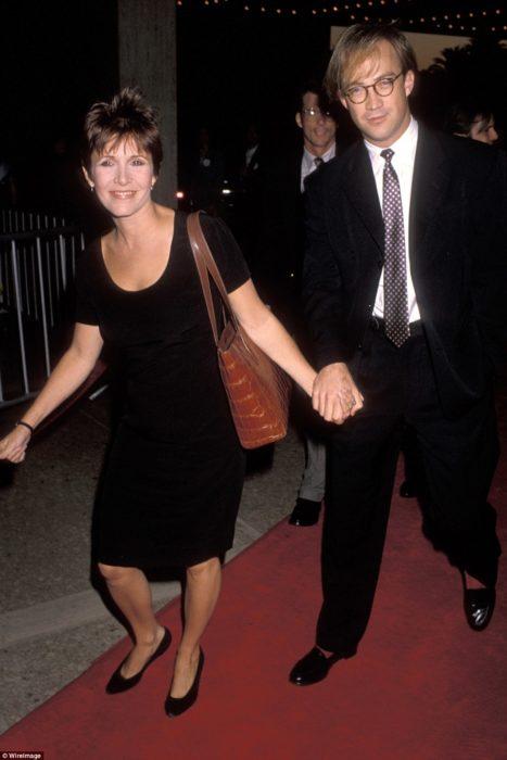 Carrie Fisher y Bryan Lourd tomados de las manos caminando por una alfombra roja