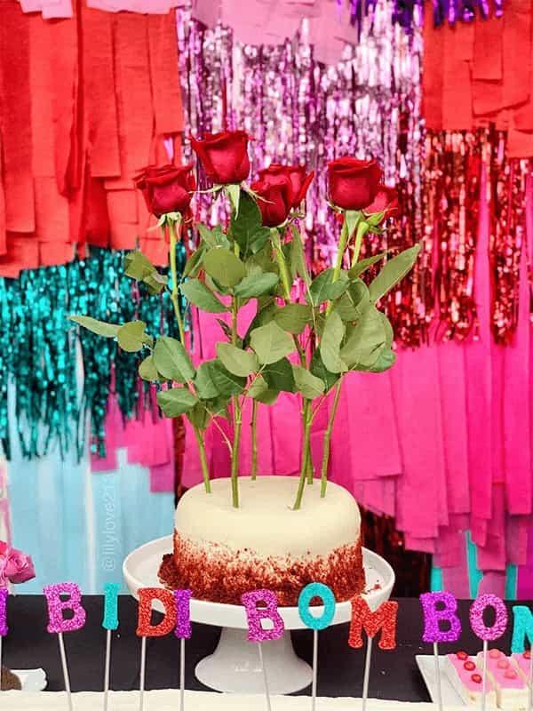 Pastel de una mesa de postres decorado con rosas y velas que dicen bidi bom bom