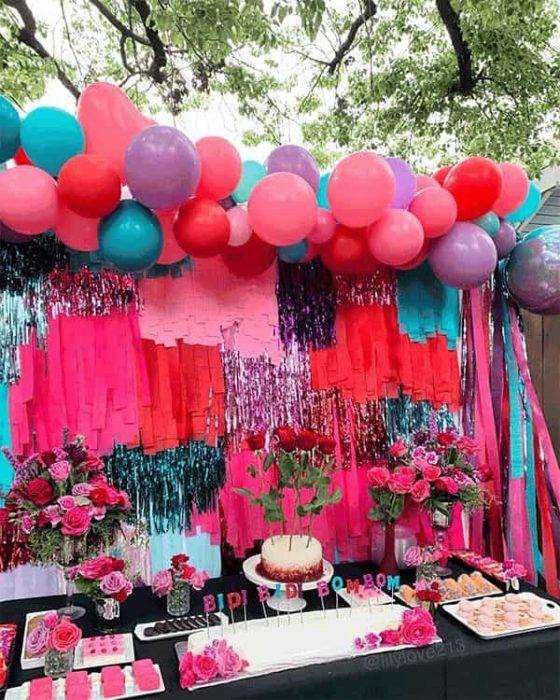 mesa de postres decorada con globos, rosas y velas que dicen bidi bidi bom bom