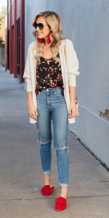 Chica caminando por la calle mientras posa con sus zapatos mocasines de color rojo