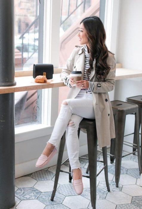 Chica sentada en un restaurante tomando un vaso de café