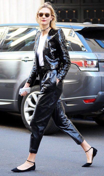 Chica caminando por la calle usando un traje negro y flats