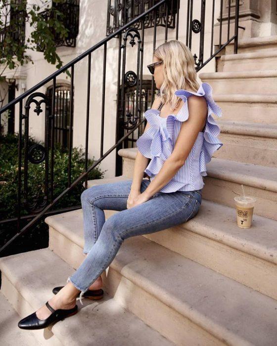 Chica sentada en unas escaleras con su bebida a un lado y mostrando su outfit