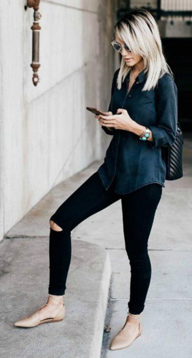 Chica parada en la calle mandando mensajes por celular