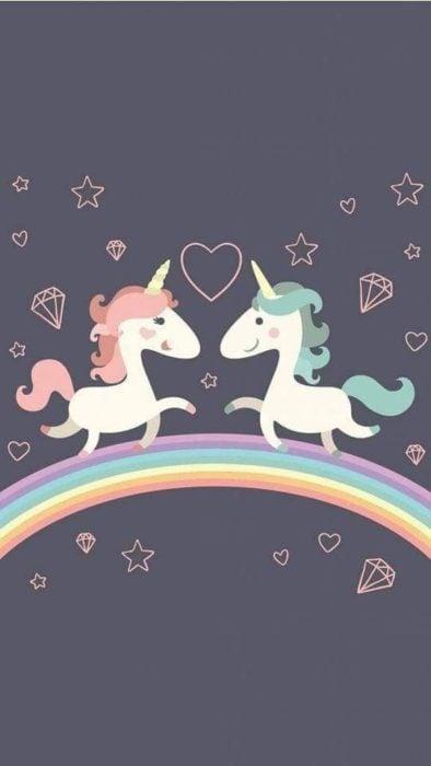 Fondo de pantalla para celular con dibujo de unicornios mirándose de frente sobre un arcoirís