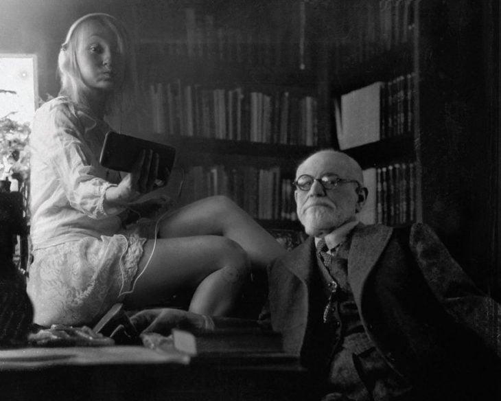 Fotógrafa Flóra Borsi tomándose una selfie con Sigmund Freud mientras están dentro de una biblioteca