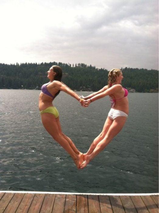 Fotos de mejores amigas que saltan y se toman de las manos y forman un corazón