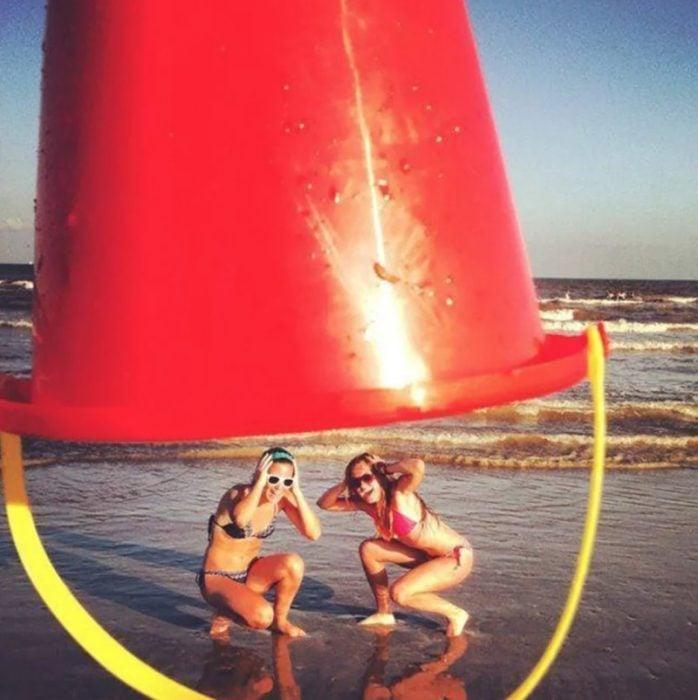 Fotos de mejores amigas; chicas intentando escapar de ser tapadas con un bote gigante mientras están en la playa